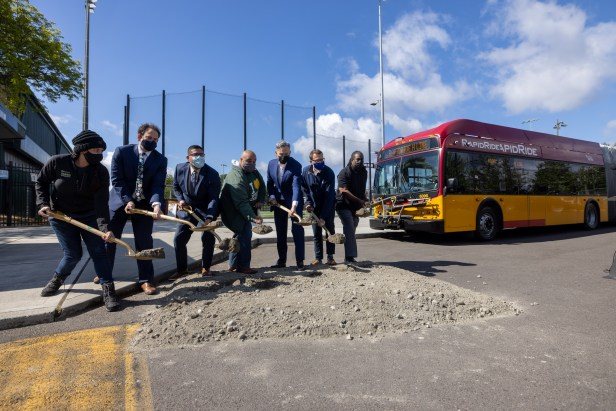 7 people holding golden shovels ceremoniously dig and turn dirt in a parking lot at Steve Cox Memorial Park near a red and yellow King County Metro RapidRide bus