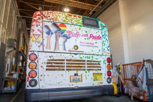 Back view of Metro's Pride bus, with Pride progress flag, hearts and rainbow colors