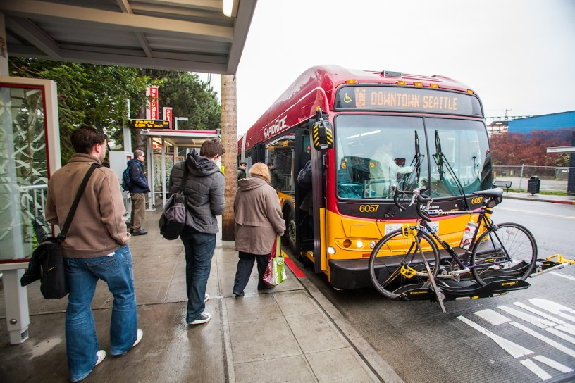 Customers board a RapidRide C Line bus heading to downtown Seattle