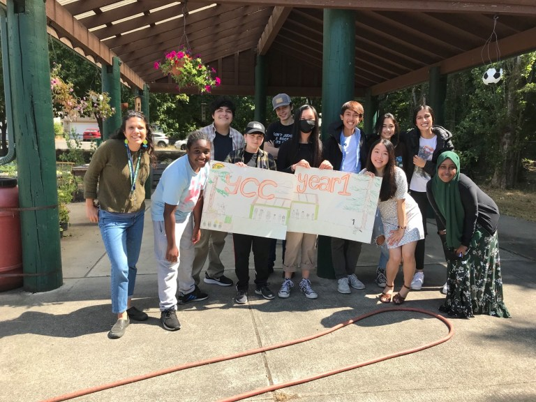 """A group of youth of all races and genders — the first cohort of the Youth Conservation Corps — stand with Sahar, a dark haired woman who is the leader of the program, in the sunshine underneath a large painted wood picnic shelter. Everyone is smiling and the youth hold 2 big hand-drawn signs that read """"YCC Year 1."""""""