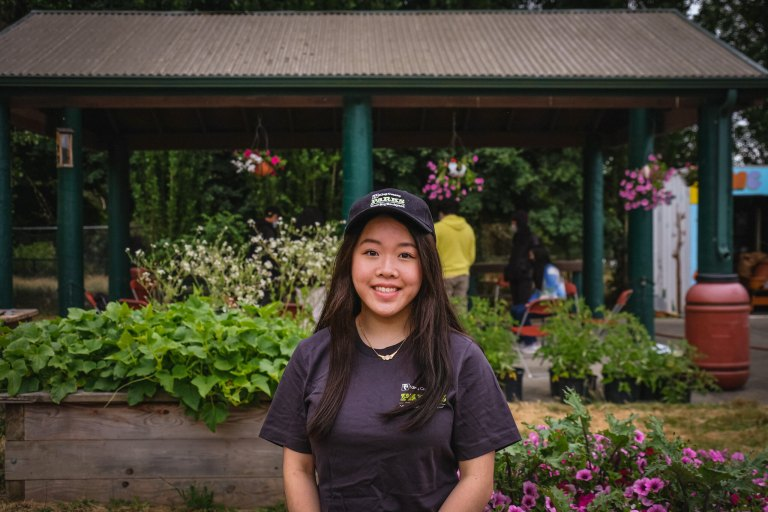 A smiling Asian girl with a King County Parks baseball cap & t-shirt on stands in front of flowers, bushes, & a picnic shelter.