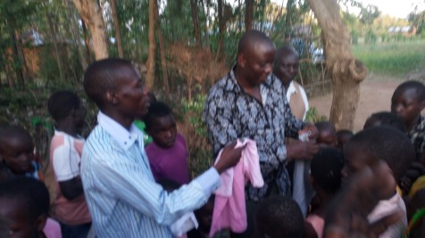 Pastor Moses and team giving clothes to orphans