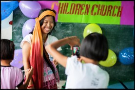 "Teacher Grace poses at the second anniversary celebration of ""Faith Haus Children's Church,"" a bible school and worship time for children from surrounding villages, held every Saturday afternoon."