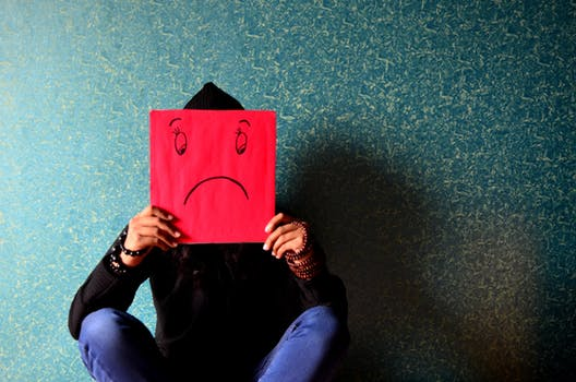 picture of a woman holding and covering herself a red cardboard with a smiley face drawn on it