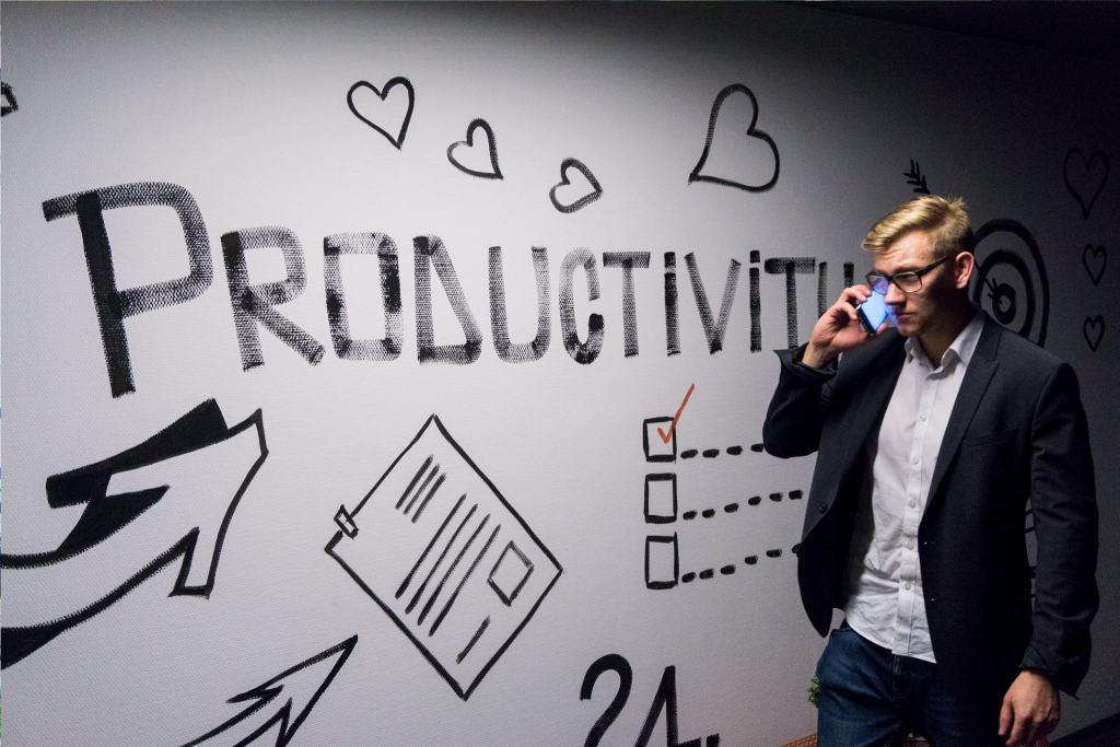 Man standing in front of a board showing life hacks to improve productivity