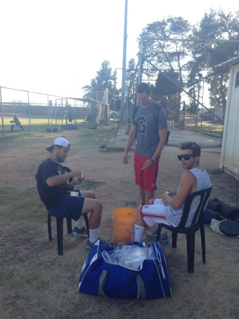 D-Ho, Vitamin AJ, and J-Max tape up whiffle balls before a National Team practice.