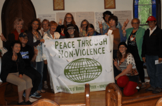 """14 attendees of the Voice of Women peace leadership camp. They hold up a banner reading """"Peace through non-violenece"""""""