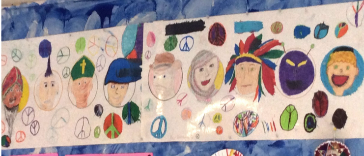A banner completed by 2014/15 PeaceQuest School participants showing peace symbols, doves, and faces of people from many cultures and continents.