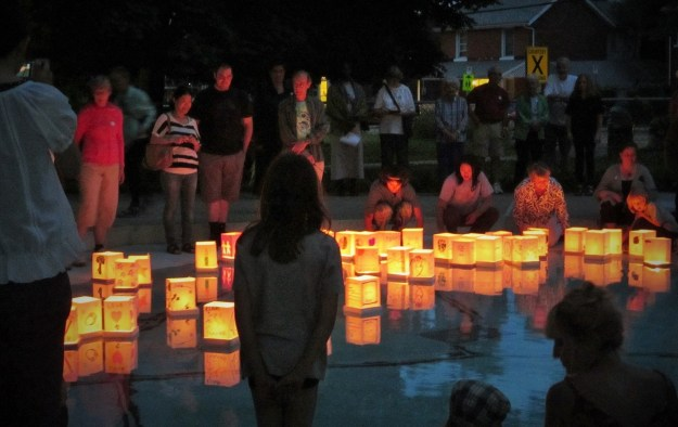 Peace Lantern Ceremony Participants gather around floating lanters in a small wading pool in Skeleton Park.