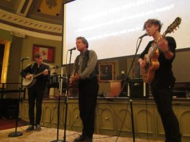 Kingston's Al Rankin -- backed-up by Liam Fenton on guitar and vocals and Kieran L'abbe on 5-string banjo -- performs John McCutcheon's song, 'Christmas in the Trenches', at an event organized by PeaceQuest-Kingston to remember the Christmas truces of 1914. It was held at Memorial Hall in December, 2014. (Photo by Jolene Simko.)