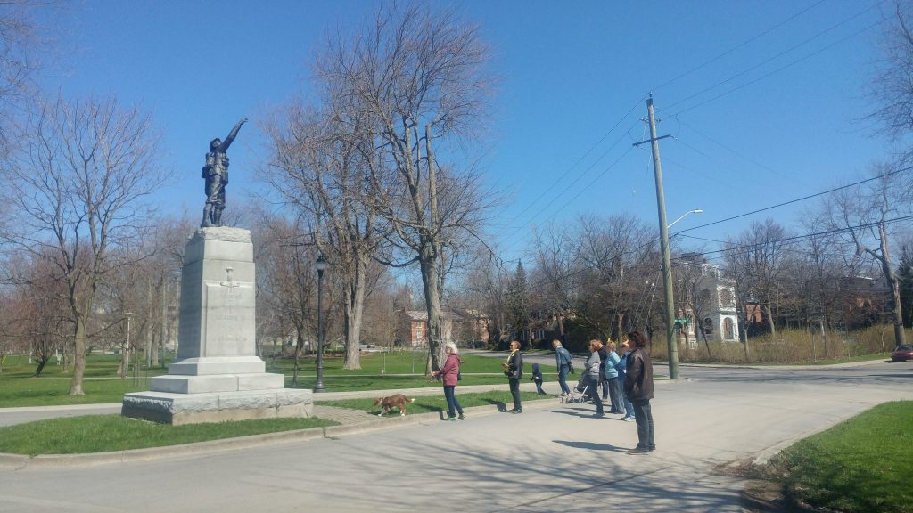 Eight individuals and a dog stand dwarfed before the twenty foot tall WWI infantry memorial in City Park, Stop 5 on the tour.