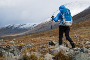 Female hiker hikes over rocky terrain in Tjäktjavagge on Kungsleden trail, Lappland, Sweden