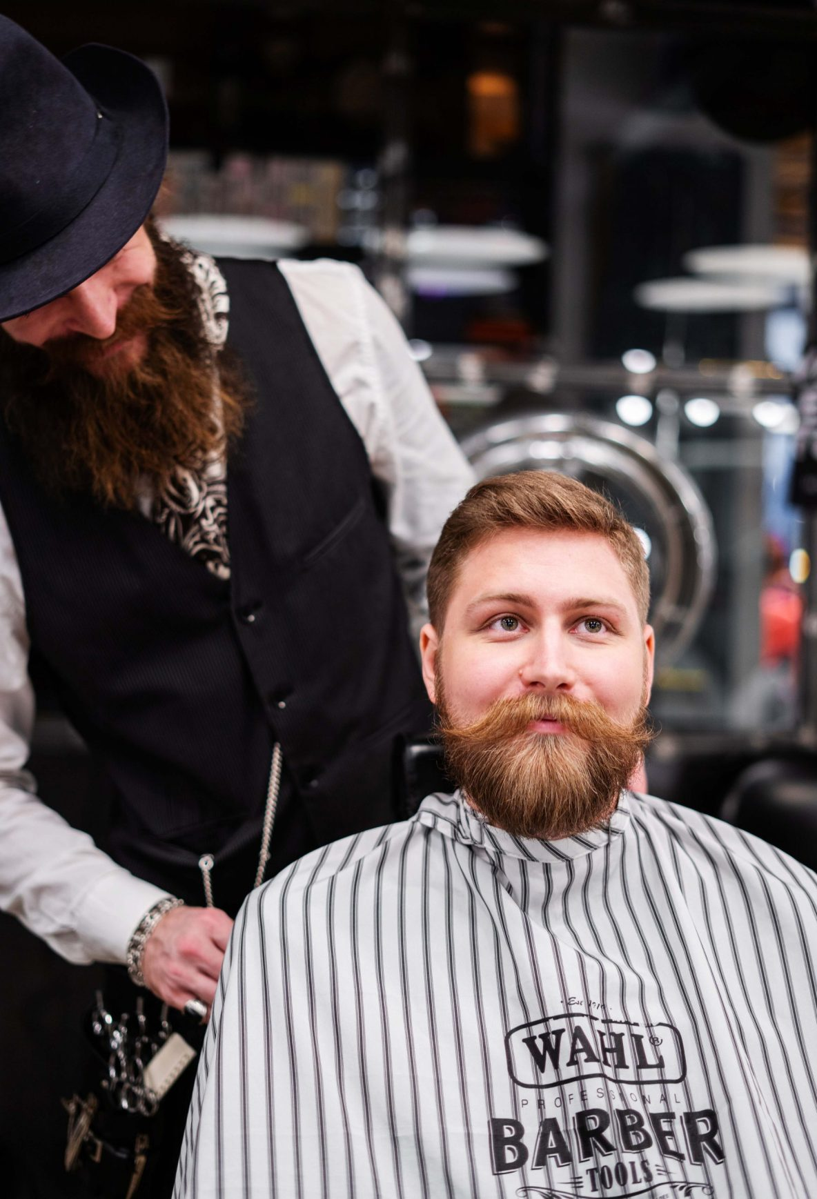 Hipster having  beard and hair trimmed by hipster barber
