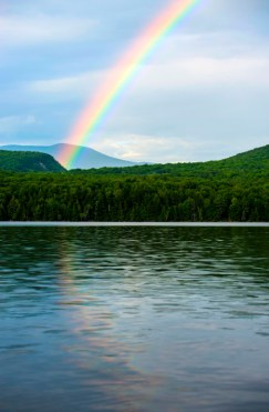 beautiful rainbow view over lake and mountains at a boys summer camp in New England
