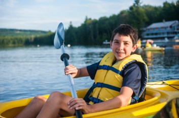 Camper happy kayaking on lake at a boys overnight summer camp in New England