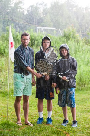 Campers playing tennis golf in the rain at a boys summer camp in New Hampshire
