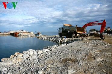 Ngay cầu cảng - cửa ngõ huyện đảo Lý Sơn (Đảo lớn), một bên là công trường kè biển đang thi công với ngổn ngang đất đá và máy móc xây dựng...