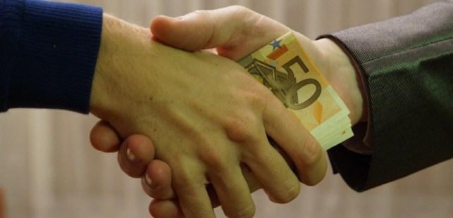 ユーロ札を握手で渡す