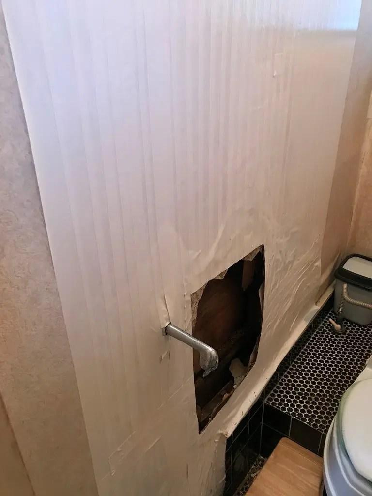トイレの壁が腐朽して穴が空いた状態の写真