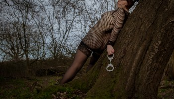 Molly wearing police hat and fishnet body stocking with handcuffs in the woods