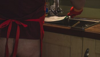 Man standing with apron on and bare bum doing the washing up for post about domestic service kink