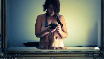 Woman taking topless picture of herself in the mirror for post about erotic photography