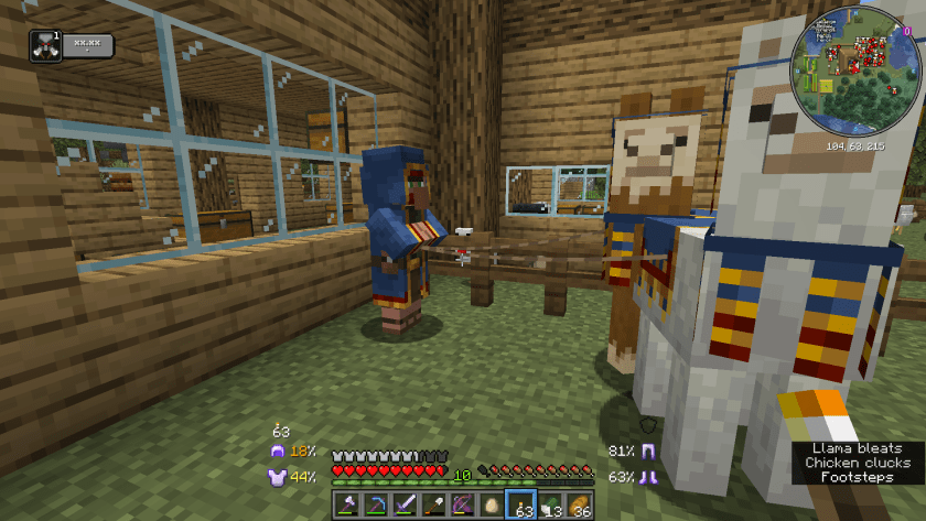 Trader with two llamas at the back of the house. They are all wearing blue cloth with red and golden accents.