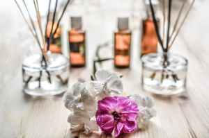 Reed diffusers and oils with a bright pink flower on a table