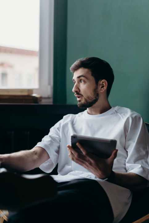 man in white crew neck t shirt holding an ipad