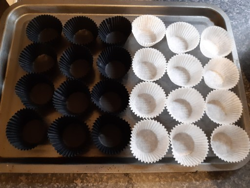 A silver metal baking tray with black and white petit fours cases laid out on it  - Bat Bites Recipe.