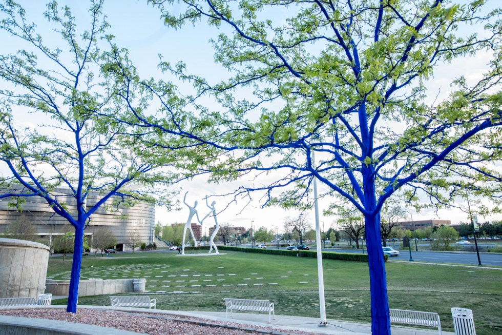 Why are the trees in Denver Blue? | Denver Photographer, big blue bear, Colorado convention center, Kon art project, blue trees, man in fishing hat, man with grey hair, portrait of Kon, artist portrait,