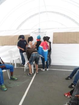 Die Jugendlichen kleben Aufkleber auf die Karte von Ciudad Blivar auf, wo sie mit Sport und Kultur in Kontakt kommen