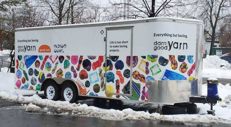 photo of a Darn Good Yarn branded travel trailer. The trailer hooks up with a hitch behind a pick up truck and carries yarn and supplies for Darn Good Yarn, also known as DGY.