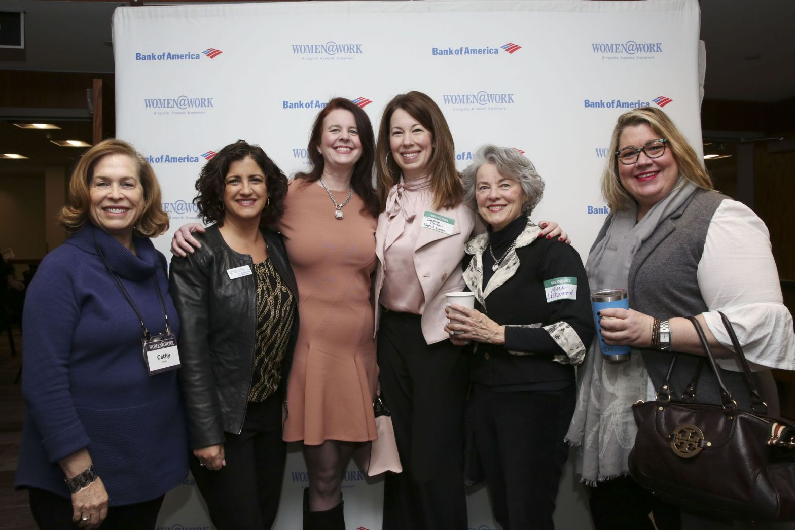 Photo of a group of smiling women in front of the logo'd step and repeat. This photo was taken while attending the Women at Work (Women@work) #networking event in February at the Hearst Times Union building located off of Wolf Road in Albany NY.