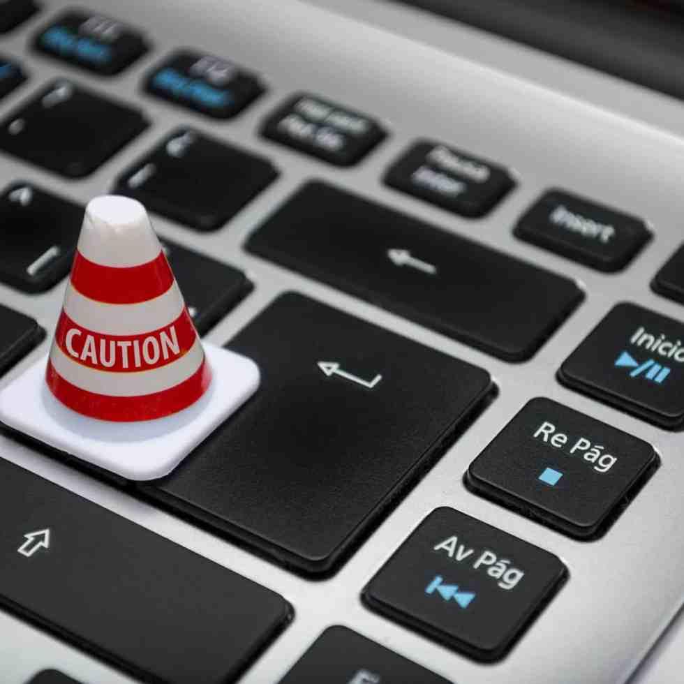 Ein Warnhütchen steht auf der Tastatur, symbolisiert die Gefahr der neuen DSVGO für Gemeinden und Kirchen