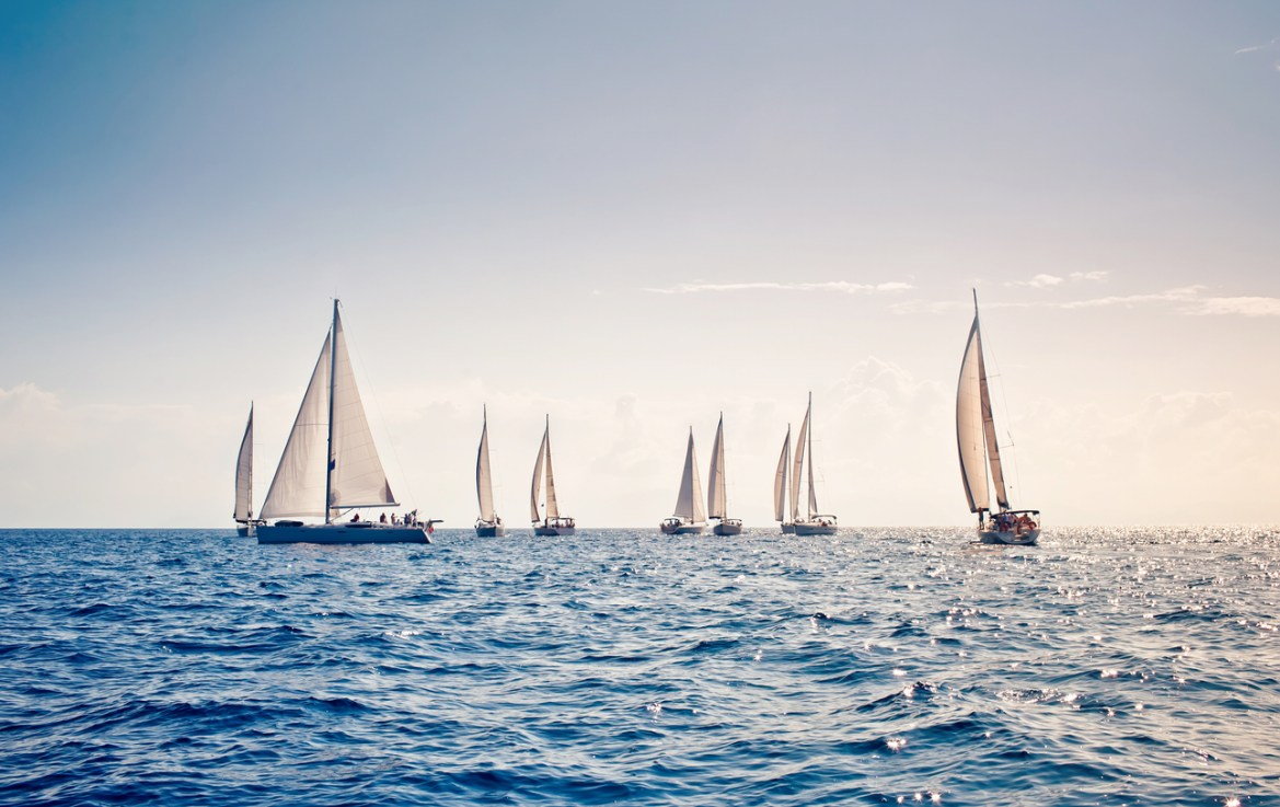 White sail sailing yachts close together in the middle of ocean