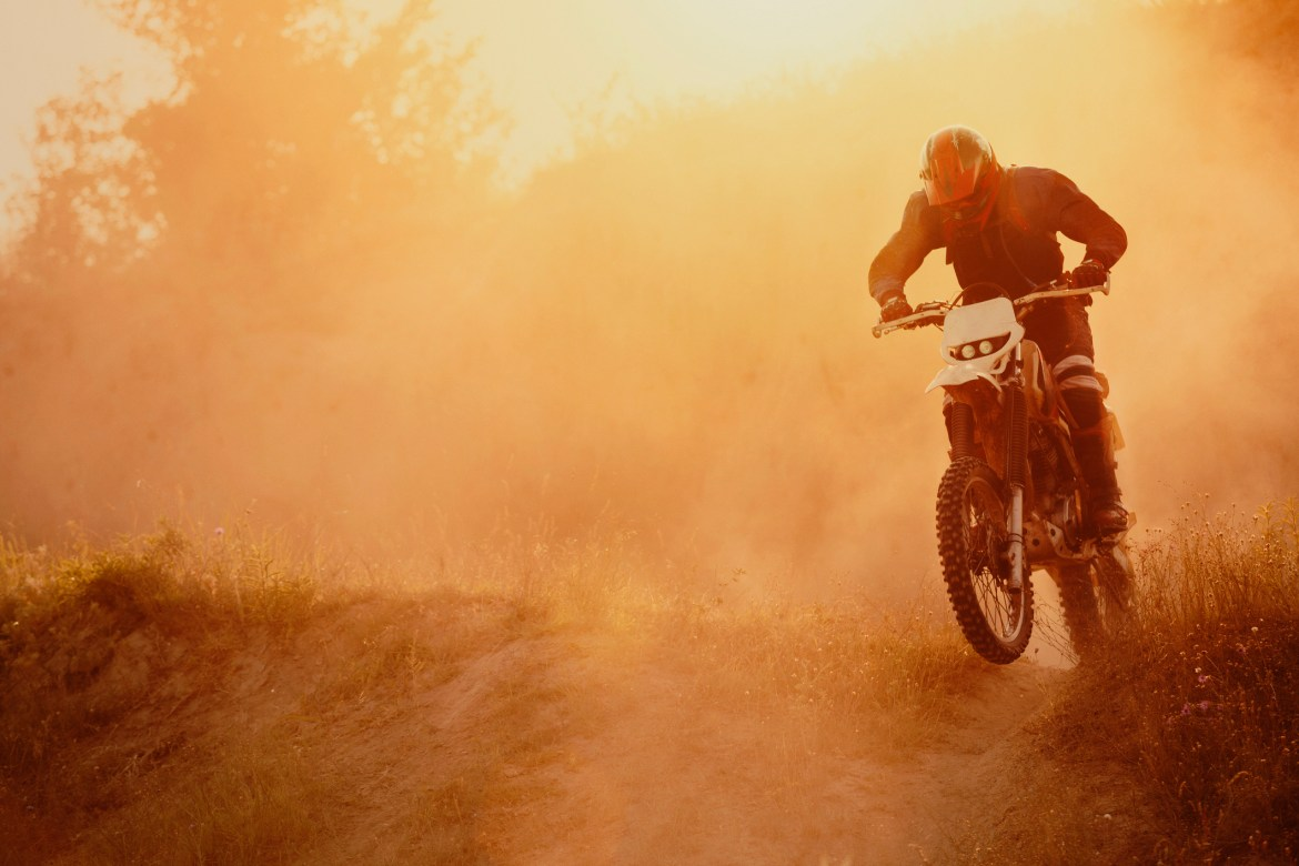 Single dirt bike rider in a dusty, smoggy atmosphere