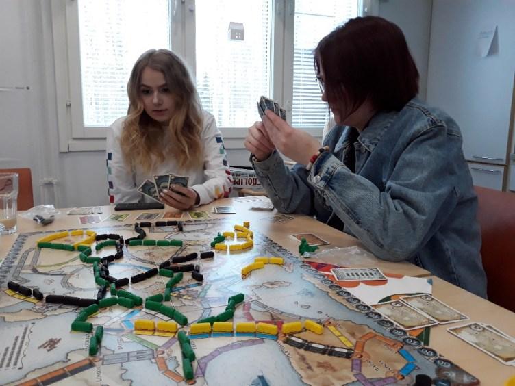 Nuoret pelaavat lautapeliä pöydän ääressä.