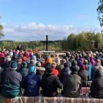 Ihmiset istuvat Kiihetlysvaaran rauniokirkon penkeillä kuuntelemassa pastori Jukka Erkkilän puhetta kirkon menettämisen muistopäivän rukoushetkessä.