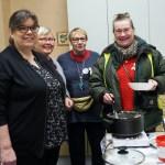 Diakoniatyöntekijä Auli Pehkonen, tarjoiluissa avustava Olga Yufa sekä Utran asukasyhdistyksen emäntä Aune Timoskainen seisovat tarjoilupöydän ääressä, Eija Nieminen ottaa kattilasta puuroa lautaselle.