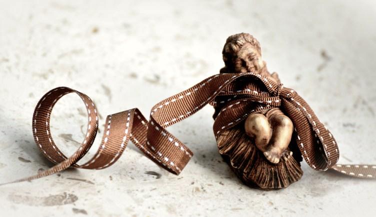 Seimiasetelman Jeesus, jonka ympärille on kääritty pakettinarusta rusetti