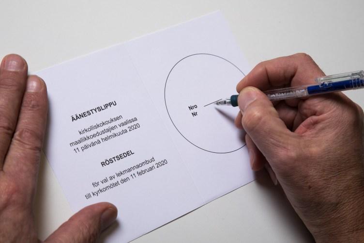 Äänestäjä pitää kynää kirkolliskokouksen maallikkoedustajien vaalissa käytettävän äänestyslipun päällä.