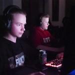 Kaksi poikaa pelaa keskittyneesti tietokoneella.
