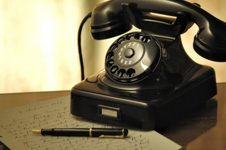 Vanhanaikainen lankapuhelin, kynä ja muistiinpanot.