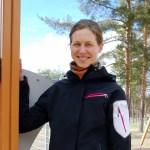 Johanna Ojala seisoo päiväkodin pihalla lasten leikkitelineen luona hynyillen.