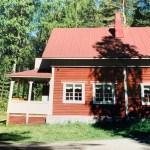 Sulkulan kesäkoti kesäisessä auringonpaisteessa. Sulkulan kesäkoti on punamullalla maalattu vanha hirsirakennus.