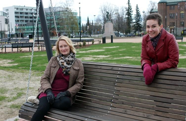 Diakoni Katja Nuuhkarinen istuu keinussa Joensuun torin laidalla ja pastori Kaisa Puustinen nojailee hymyillen keinun selkämykseen.