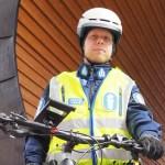 Polkupyöräpoliisi seisoo Joensuun torilavan edessä.