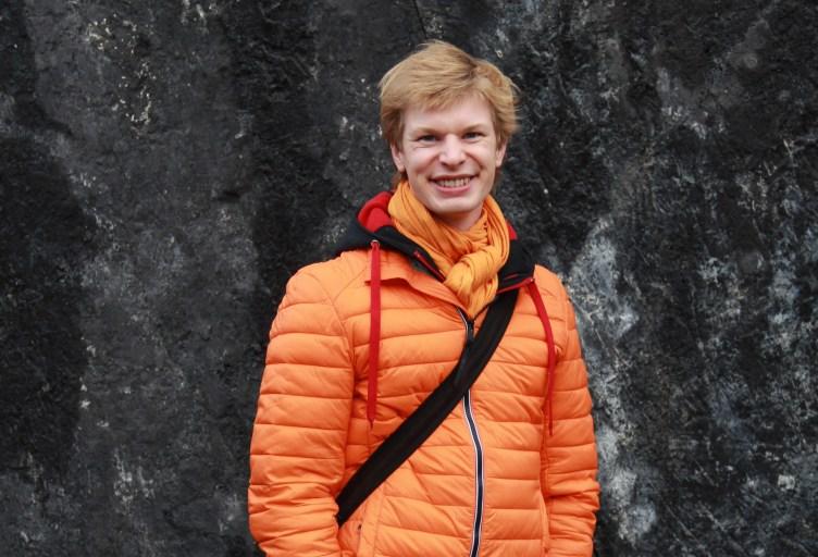 Ylikapellimestari Eero Lehtimäki seisoo kivipaaden edessä ja katsoo kameraan hymyillen.