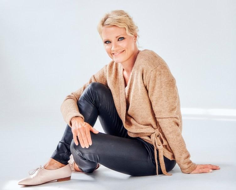 Maaret Kallio istuu lattialla ja katsoo hymyillen kameraan.